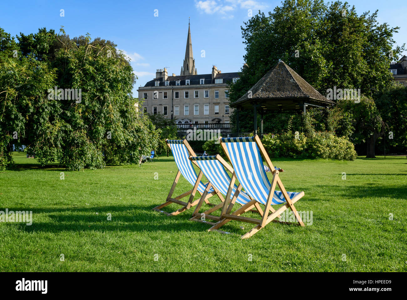 Bandstand and loungers  in the Parade Gardens and Bath Abbey. Bath, Somerset, England - Stock Image