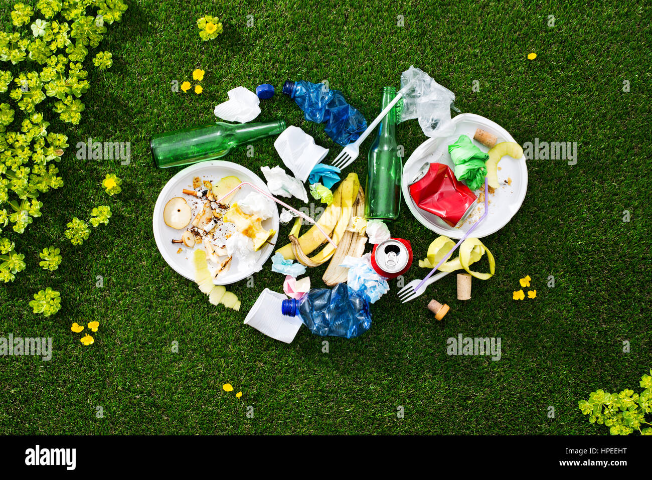 Load of mixed rubbish left on the grass after a picnic, environmental care and waste concept - Stock Image