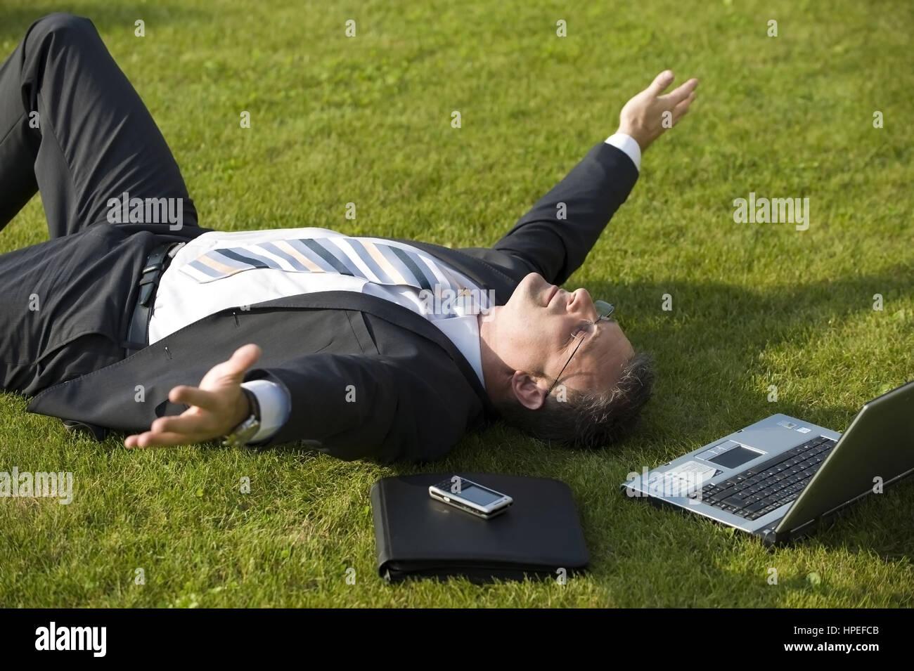 Model released , Geschaeftsmann rastet in der Wiese - businessman relaxing in meadow Stock Photo