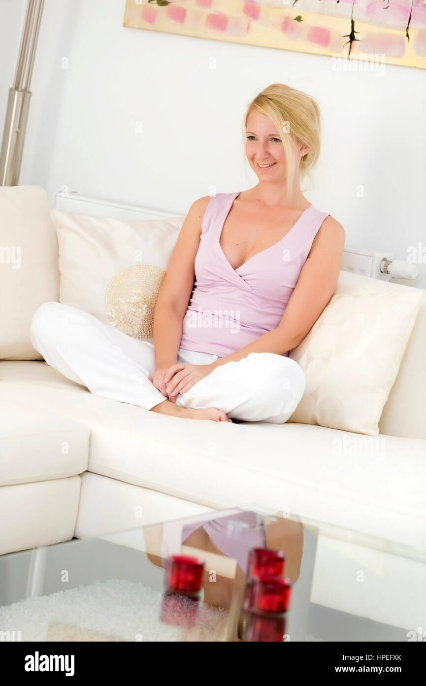 Model released , Blonde, attraktive Frau, 35, sitzt gemuetlich auf Couch - blond woman sitting on couch - Stock Image