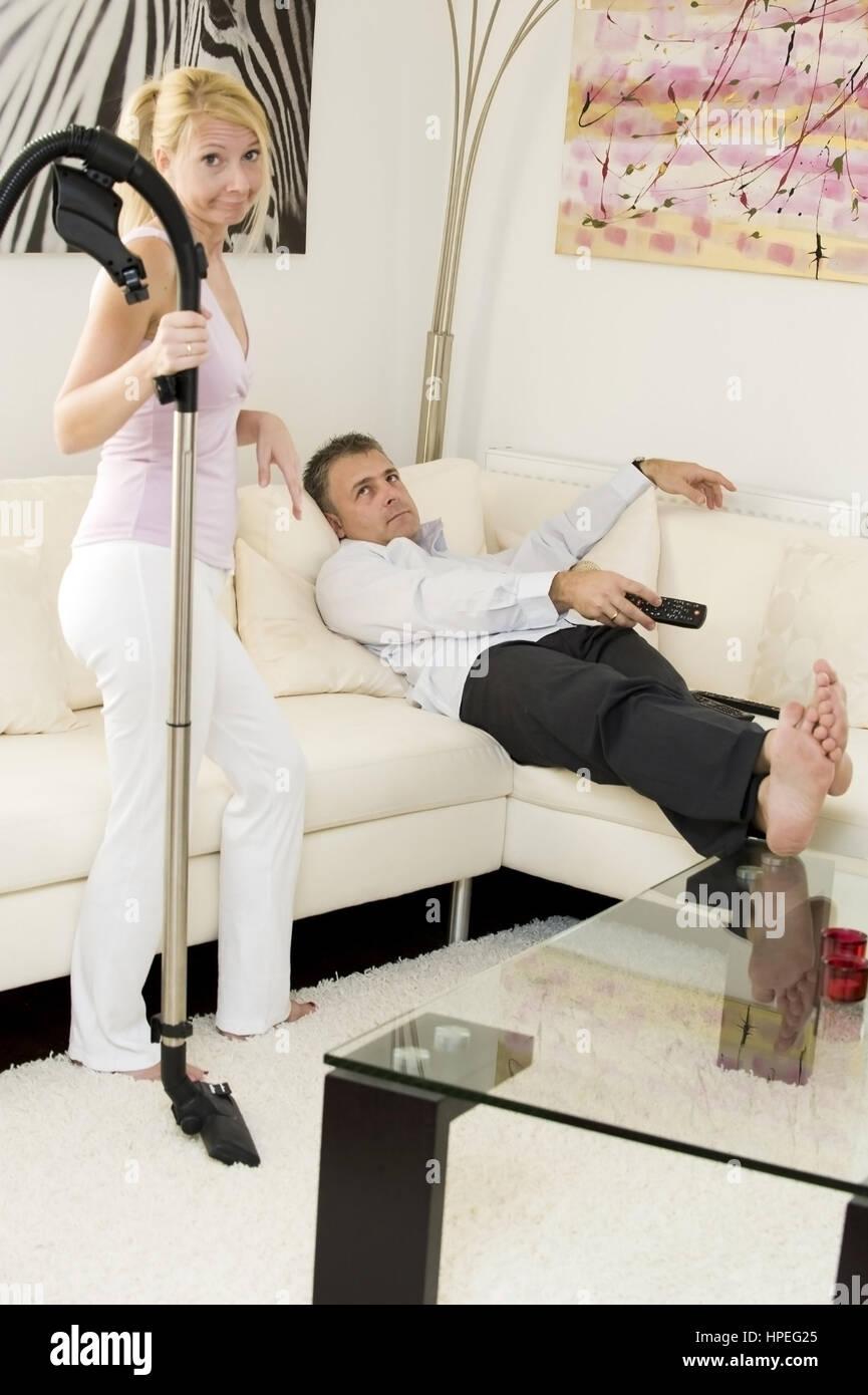 Model released , Frau beim Staubsauegn, Mann liegt auf der Couch und sieht fern - woman does hoovering, man watching Stock Photo