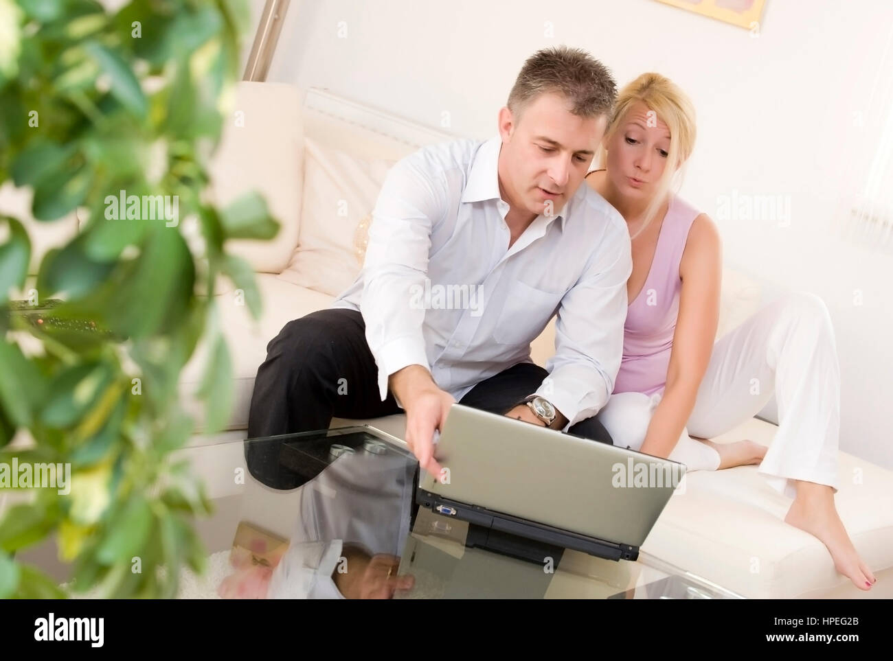 Model released , Paar sitzt mit Laptop auf Couch im Wohnraum - couple using laptop Stock Photo