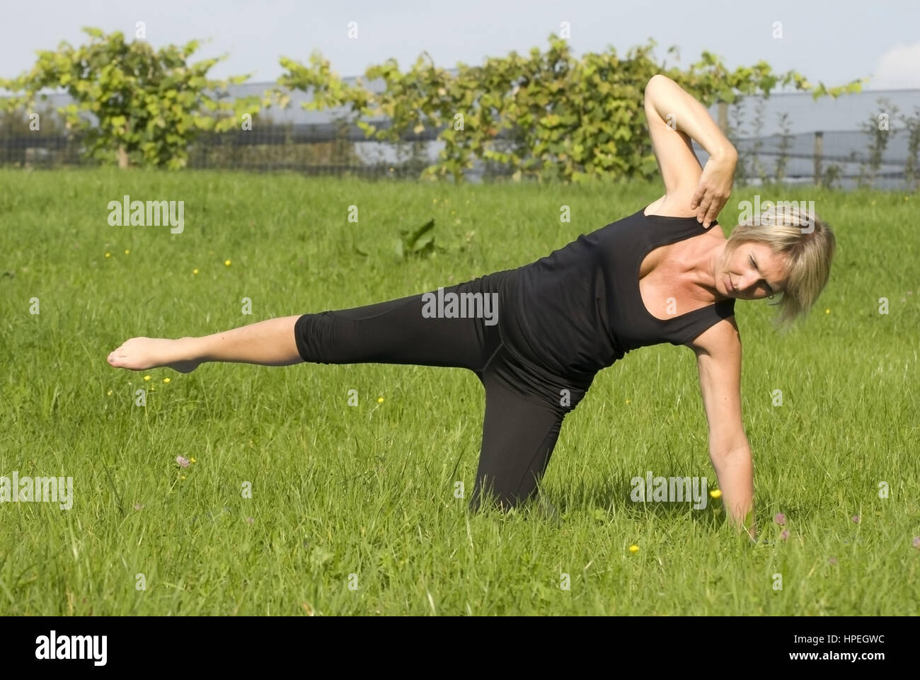 Frau macht Pilates in der Wiese - woman does pilates in meadow - Stock Image