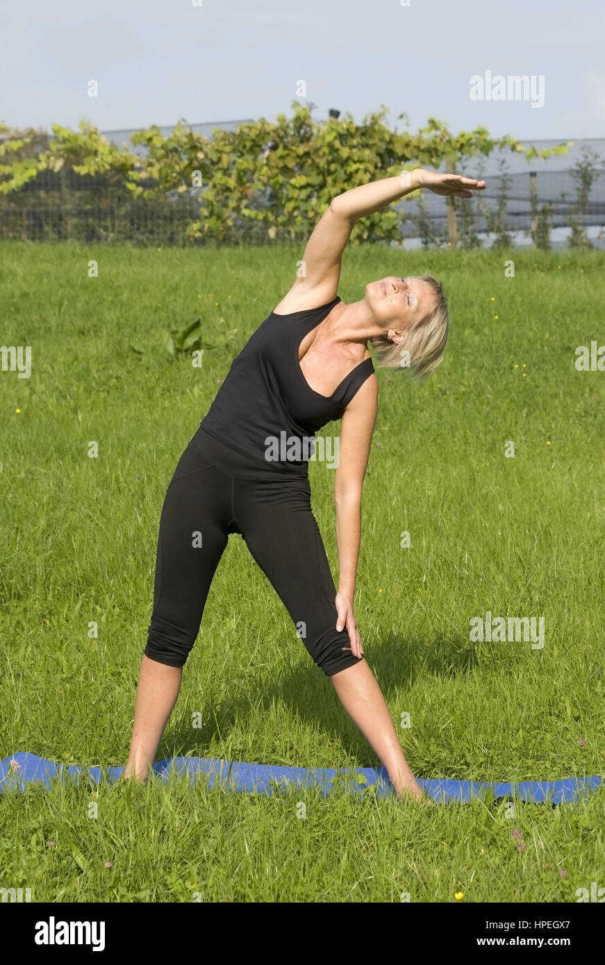 Frau beim Stretching in der Wiese - woman does stretching in meadow - Stock Image