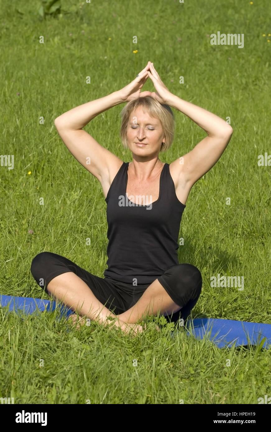 Frau macht Joga in der Wiese - woman does yoga in meadow - Stock Image
