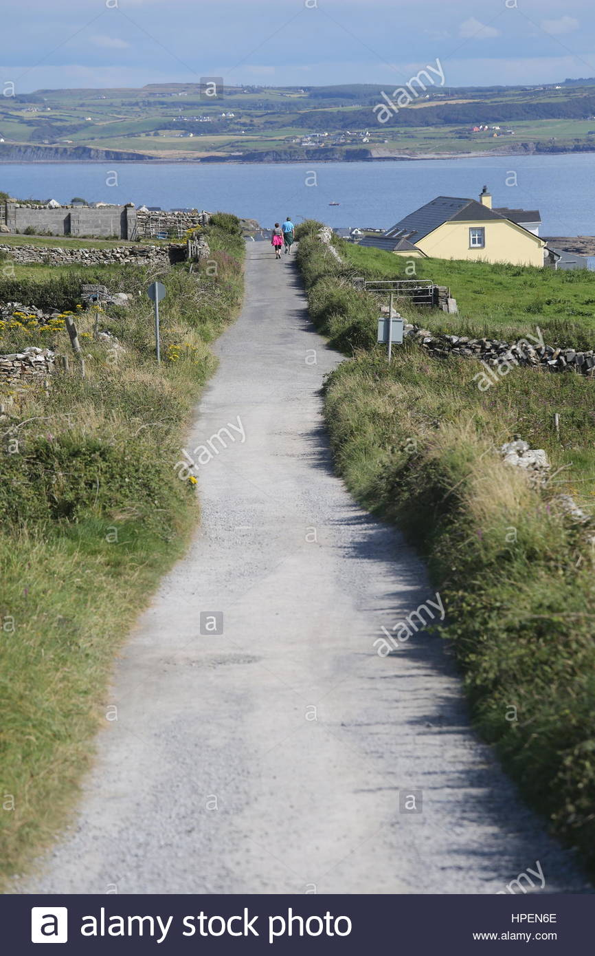 A lonely road on a sunny day in the West of Ireland with the ocean visible in the background. - Stock Image
