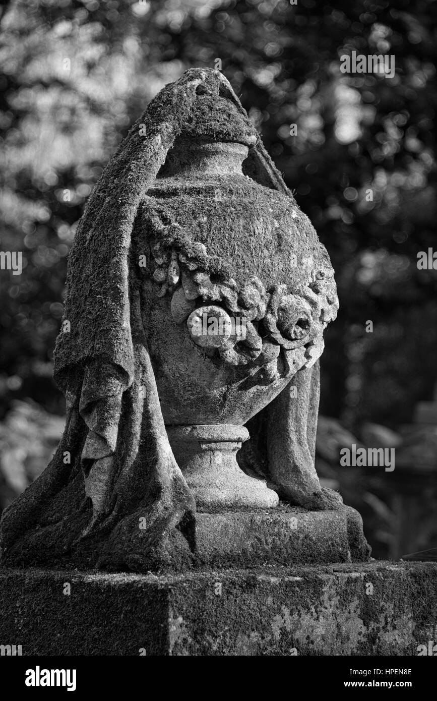 Half covered draped urn tombstone gravestone Greek tradition for spirit to escape at Highgate Cemetery - Stock Image