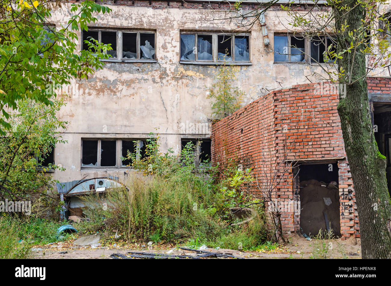 Unattended destroyed and devastated building with broken windows, smashed doors and scrap over the imbruted lot - Stock Image