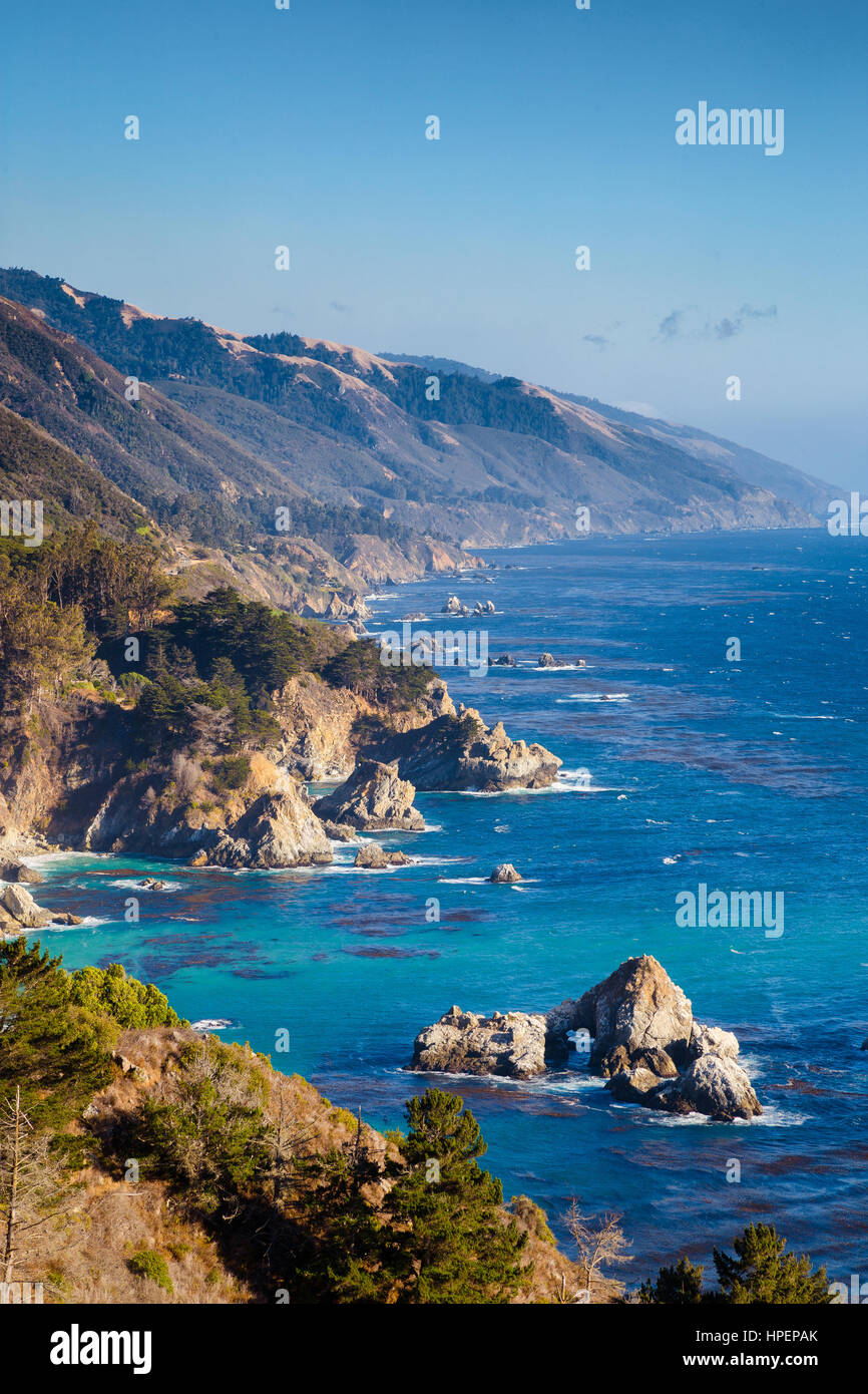Scenic view of the rugged coastline of Big Sur with Santa Lucia Mountains along famous Highway 1 in beautiful evening - Stock Image