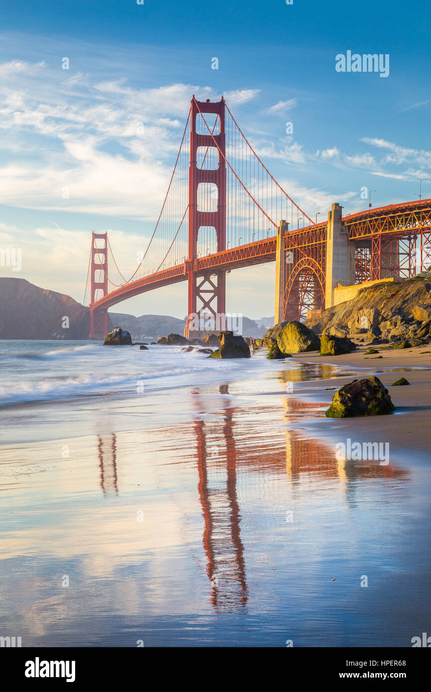 Classic vertical view of famous Golden Gate Bridge seen from scenic Baker Beach in beautiful golden evening light - Stock Image