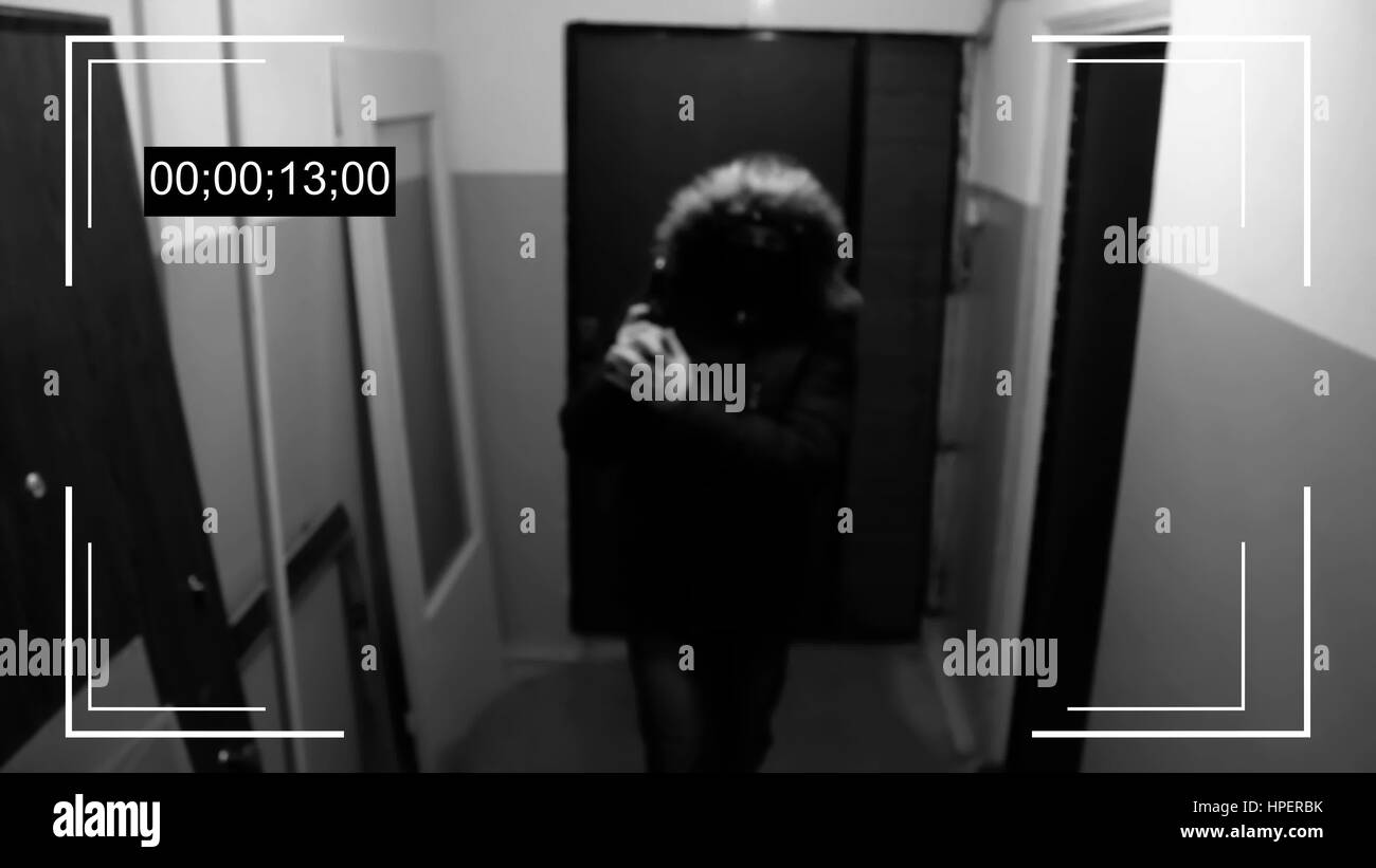 an armed young man in the mask breaks the door and smashes the security camera and handle a gun - Stock Image
