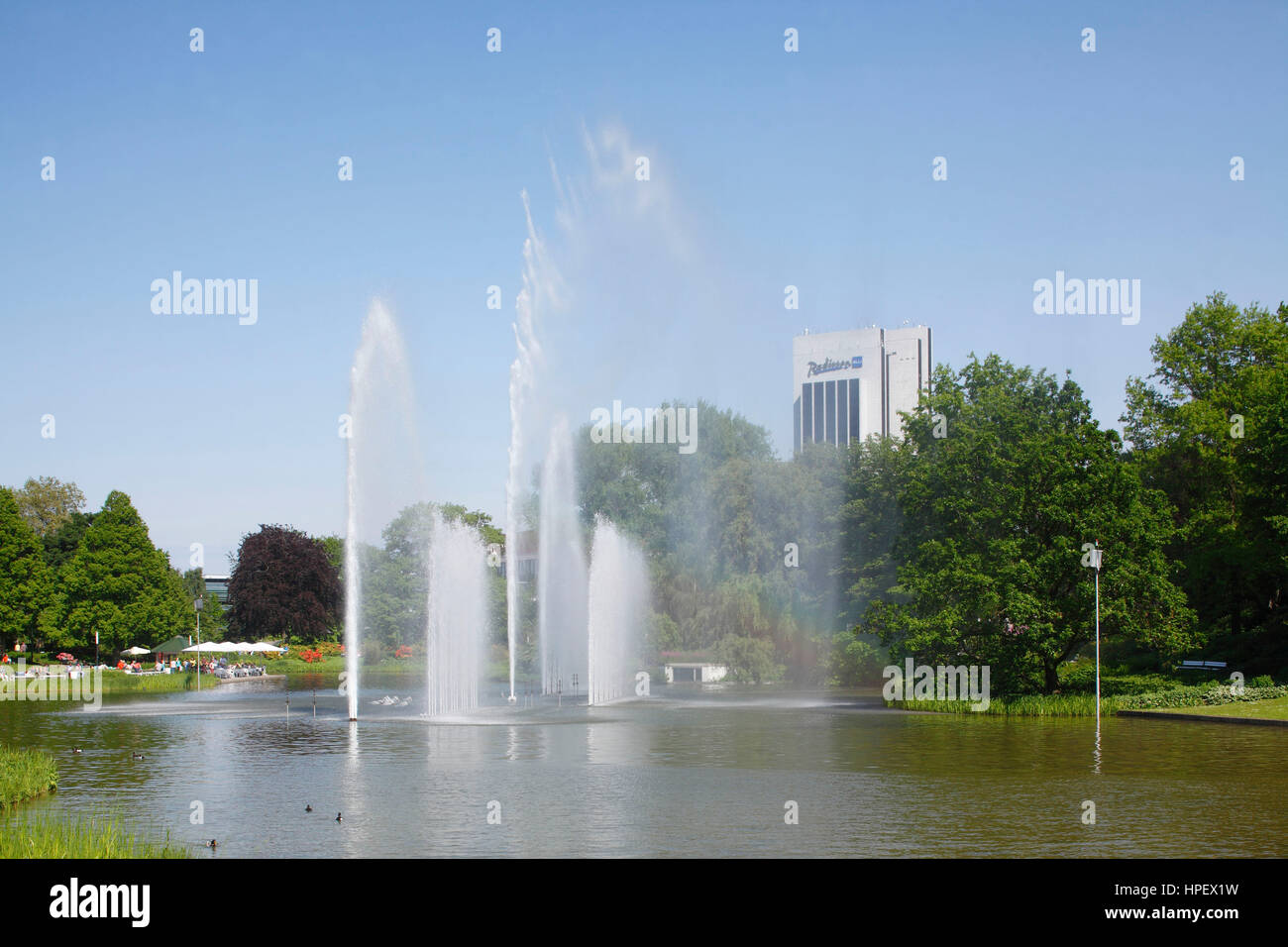 Pond, trick fountains, Radisson Blu Hotel and Park Planten un Blomen, Hamburg, Germany, Europe - Stock Image