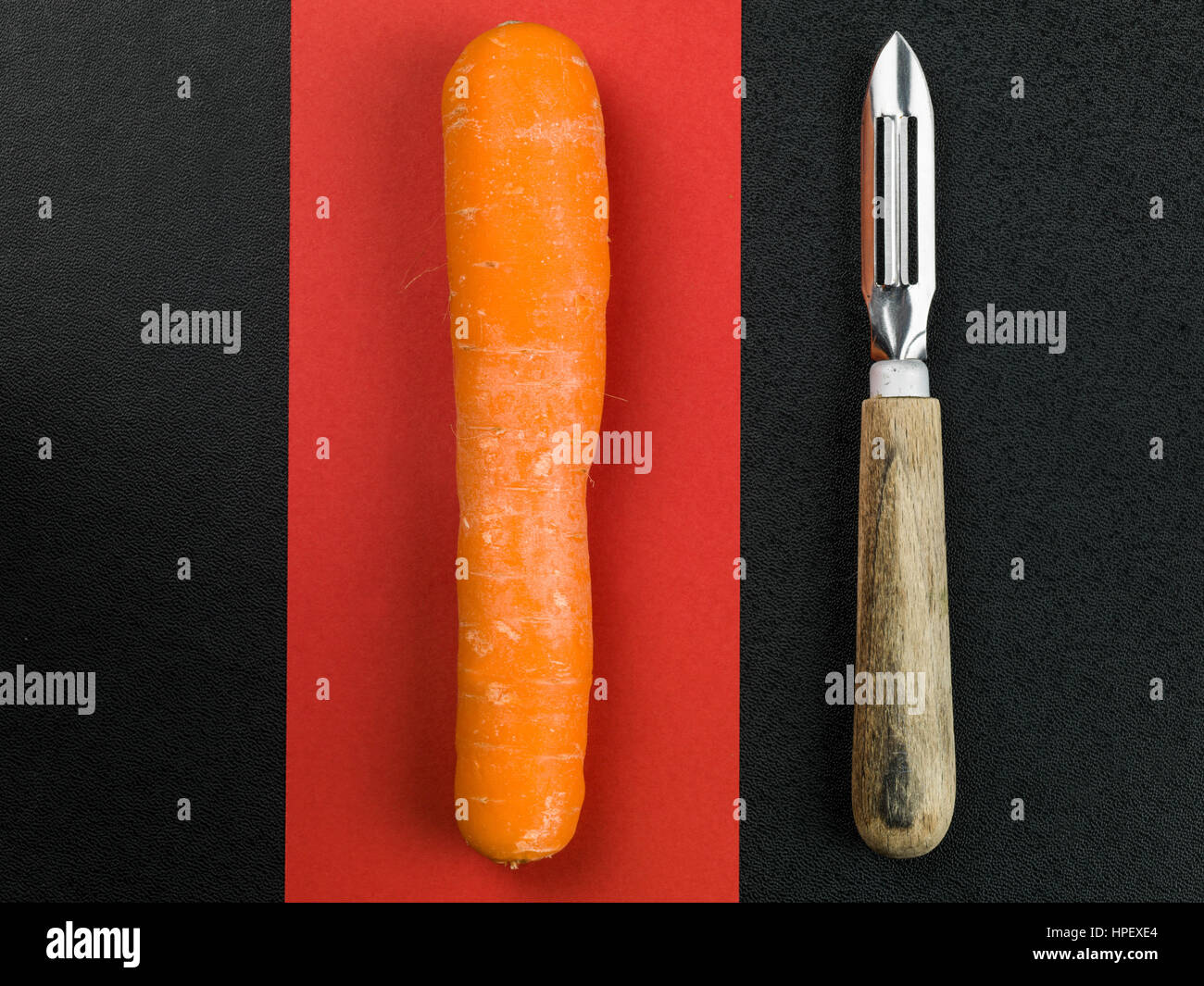 Raw Carrot With a Wooden Handled Vegetable Peeler - Stock Image