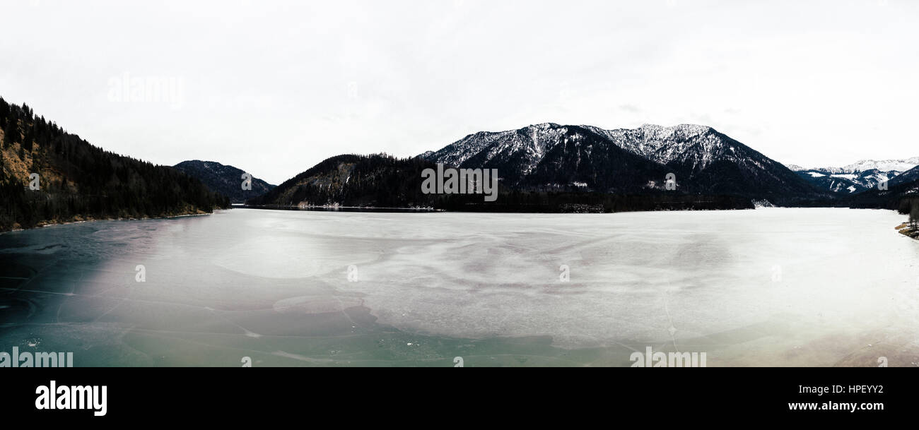 Mountain panorama in Bavaria with view to the alps and a frozen lake, muted colours, wintry cold scenario, deserted, - Stock Image