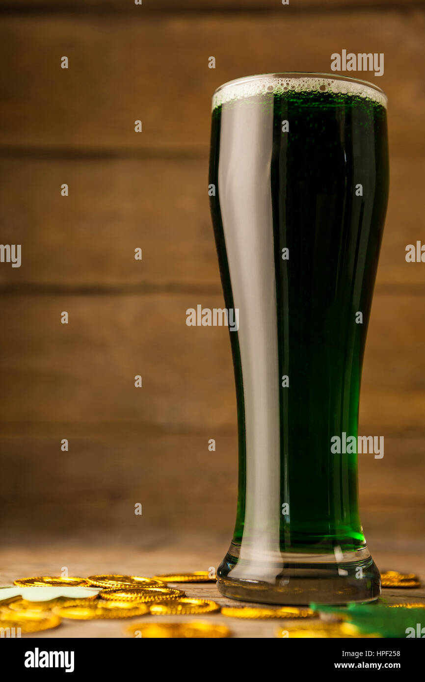 Glass of green beer, chocolate gold coins and shamrock for St Patricks Day on wooden table - Stock Image