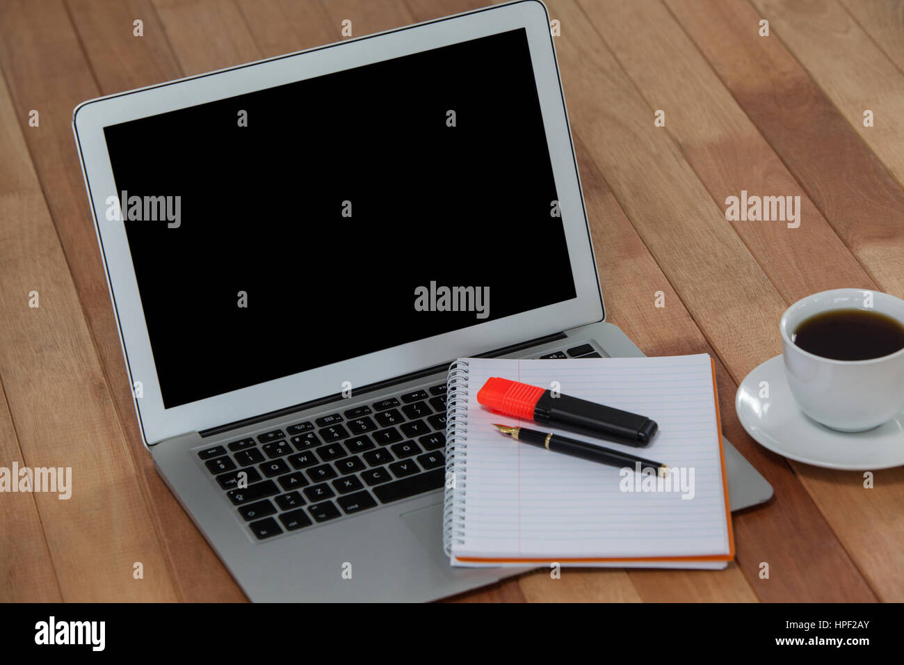 Cup Of Coffee With Laptop Organizer Maker And Pen On Wooden
