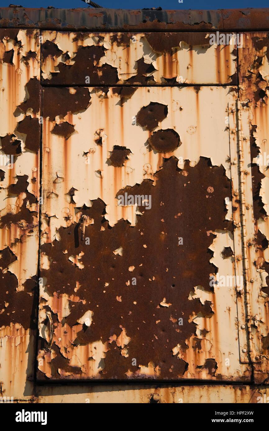Rusted door on yellow cab of old excavator machine. - Stock Image