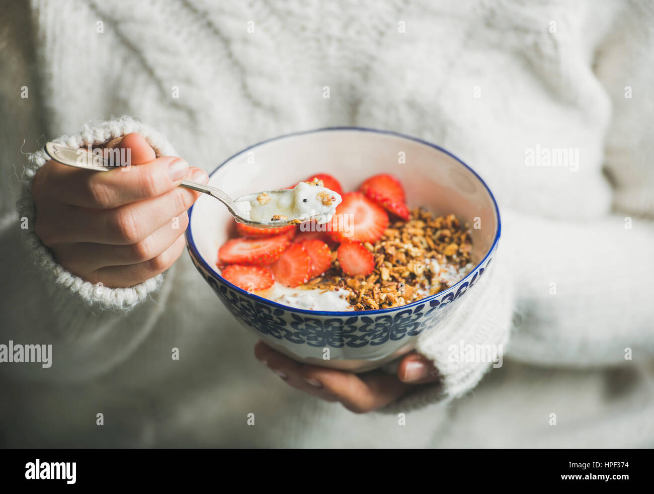 Healthy breakfast greek yogurt, granola and strawberry bowl in hands of woman wearing white loose knitted woolen - Stock Image