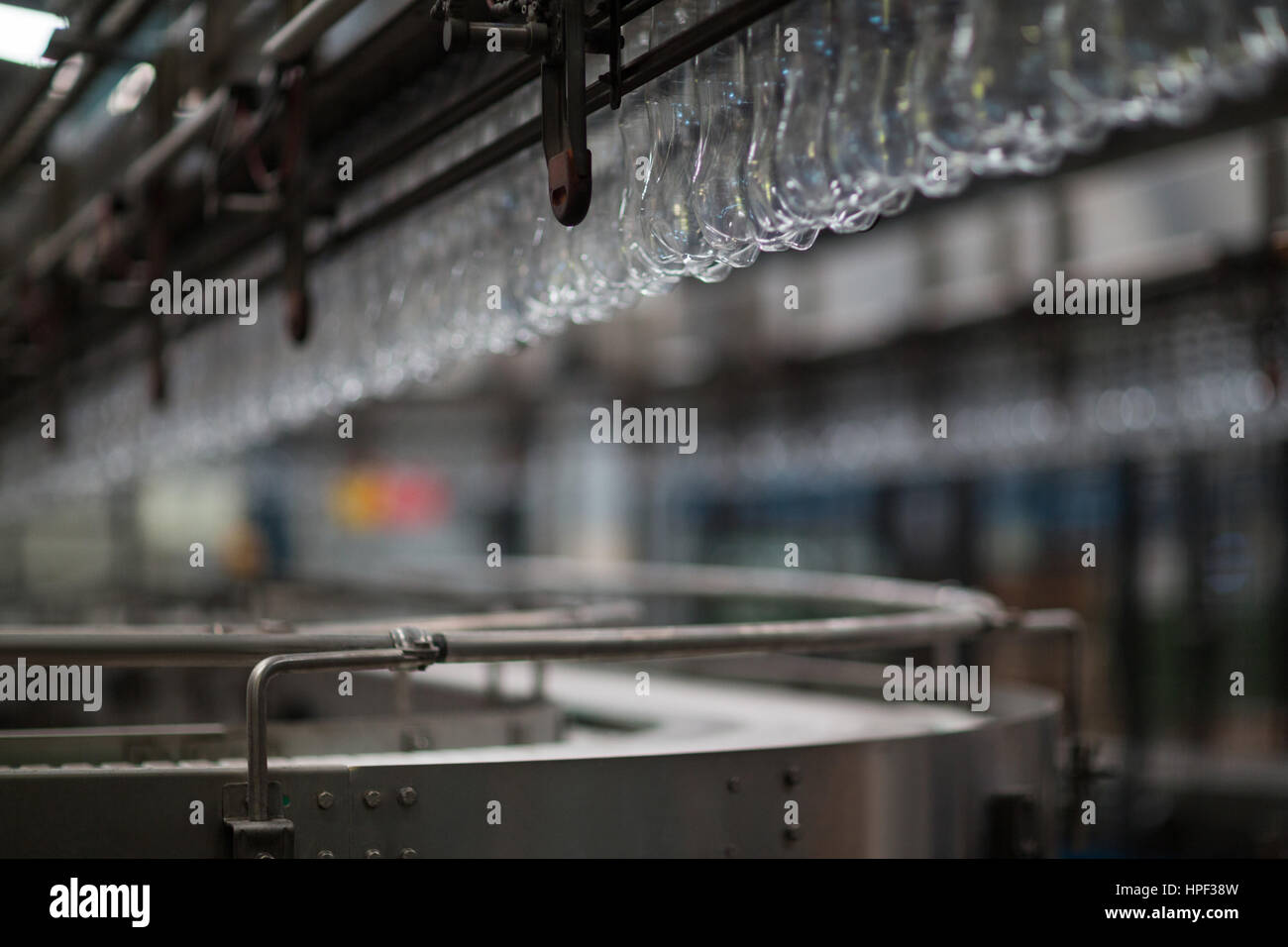Empty bottles moving on production line in drinks production plant Stock Photo