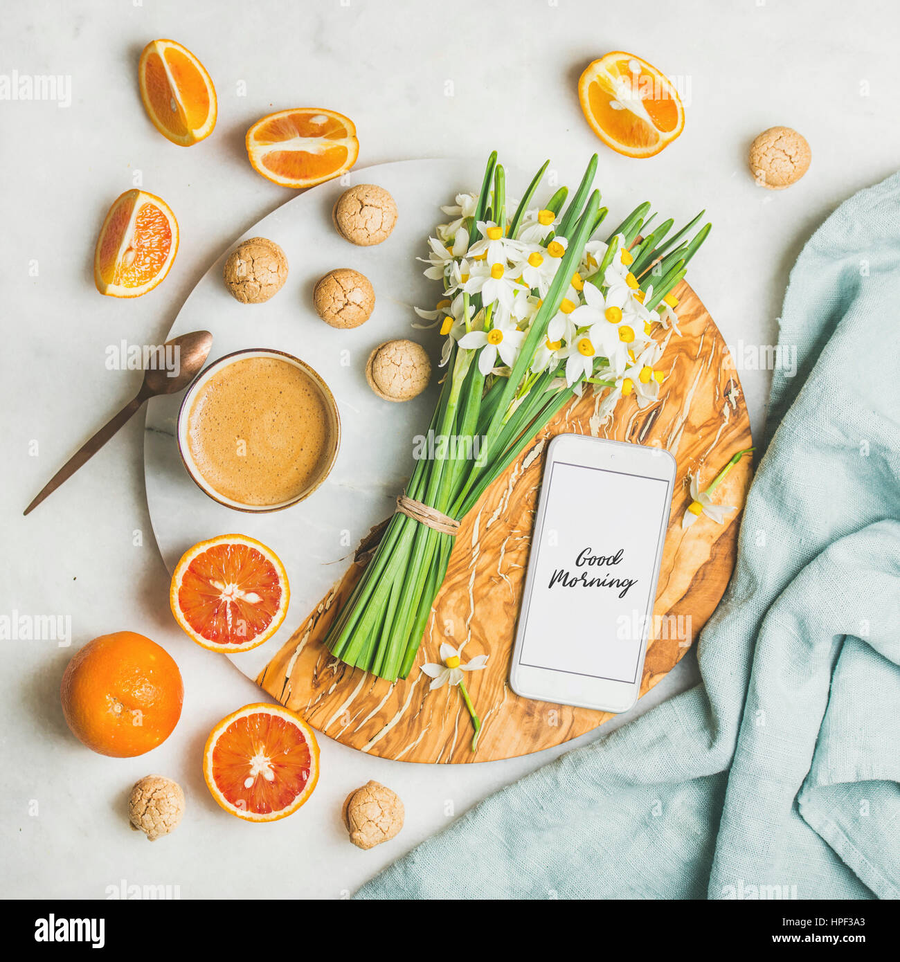 Cup of morning coffee, cookies, red oranges and bucket of spring flowers and mobile phone with text Good morning - Stock Image