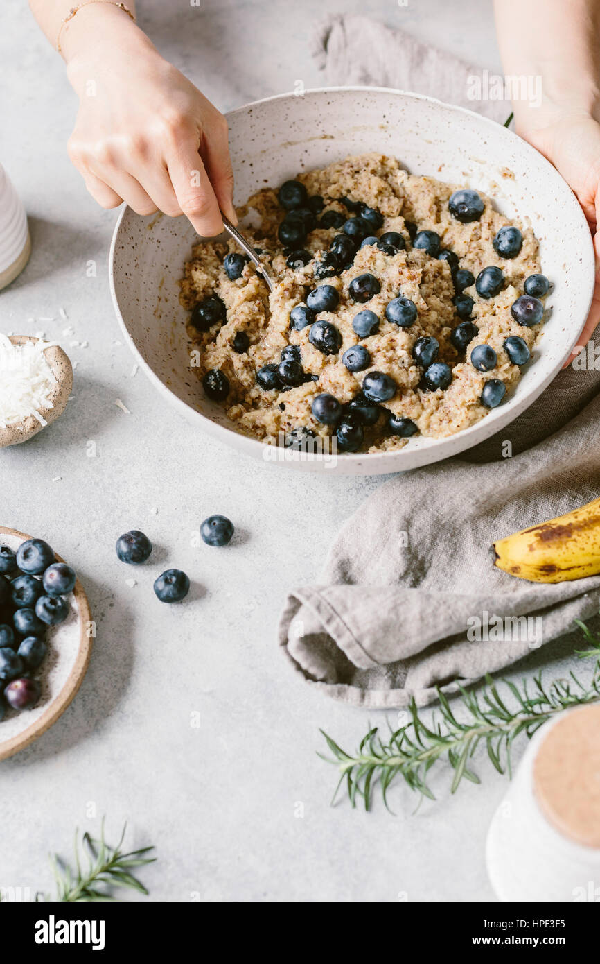 A woman's hands are photographed as she is mixing blueberry muffin batter. Stock Photo