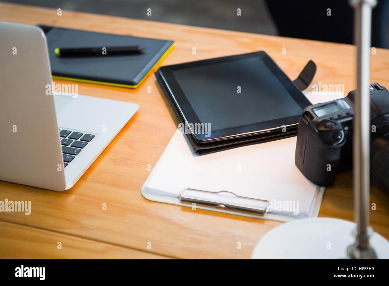Close-up of laptop, digital tablet and digital camera on desk - Stock Image