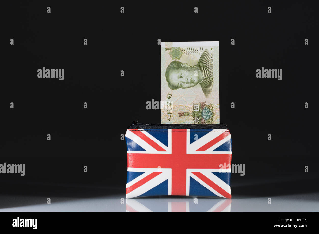Union Jack coin purse with Chinese Yuan / Renminbi ... against a dark background. Metaphor for Yuan-Pound exchange - Stock Image