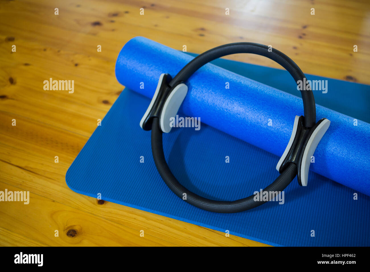 Pilates ring and exercise mat kept on wooden floor in fitness center - Stock Image