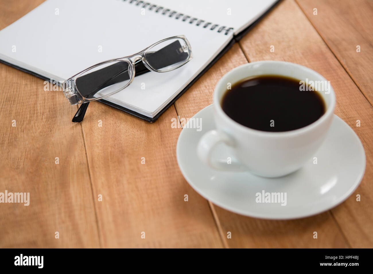Open diary with spectacle and black coffee on table - Stock Image