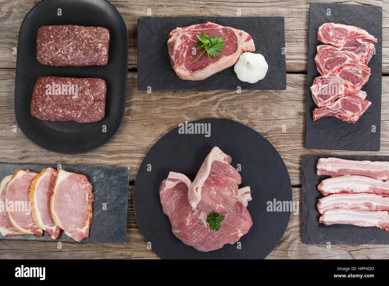 Varieties of meat on black tray against wooden background - Stock Image