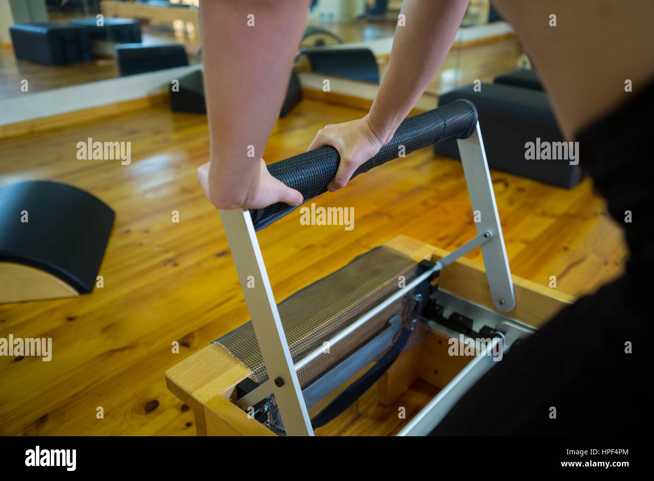 Mid section of woman exercising on reformer in gym - Stock Image