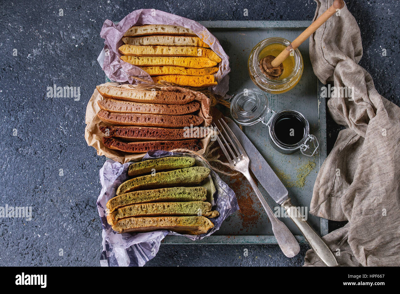Variety of sliced american ombre chocolate, green tea matcha and turmeric pancakes served in paper paper wrapper - Stock Image