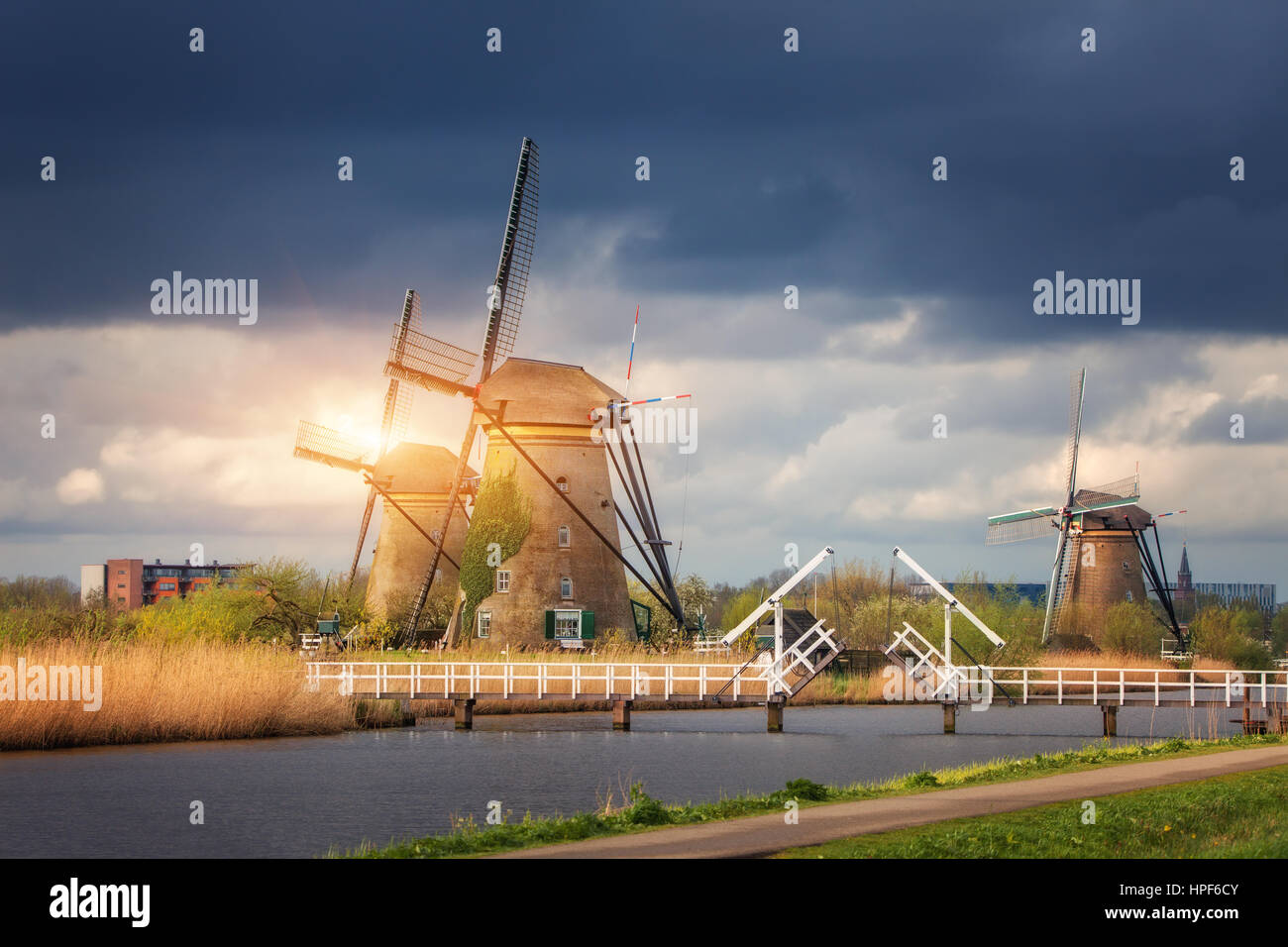 Windmills against cloudy sky at sunset in famous Kinderdijk, Netherlands. Rustic landscape with traditional dutch - Stock Image