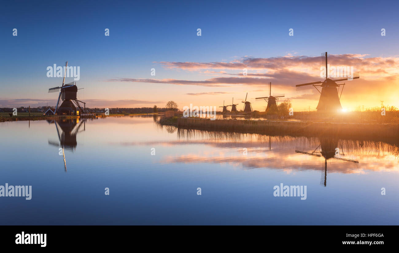 Silhouette of windmills at amazing foggy sunrise in Kinderdijk, Netherlands. Rustic landscape with dutch windmills - Stock Image