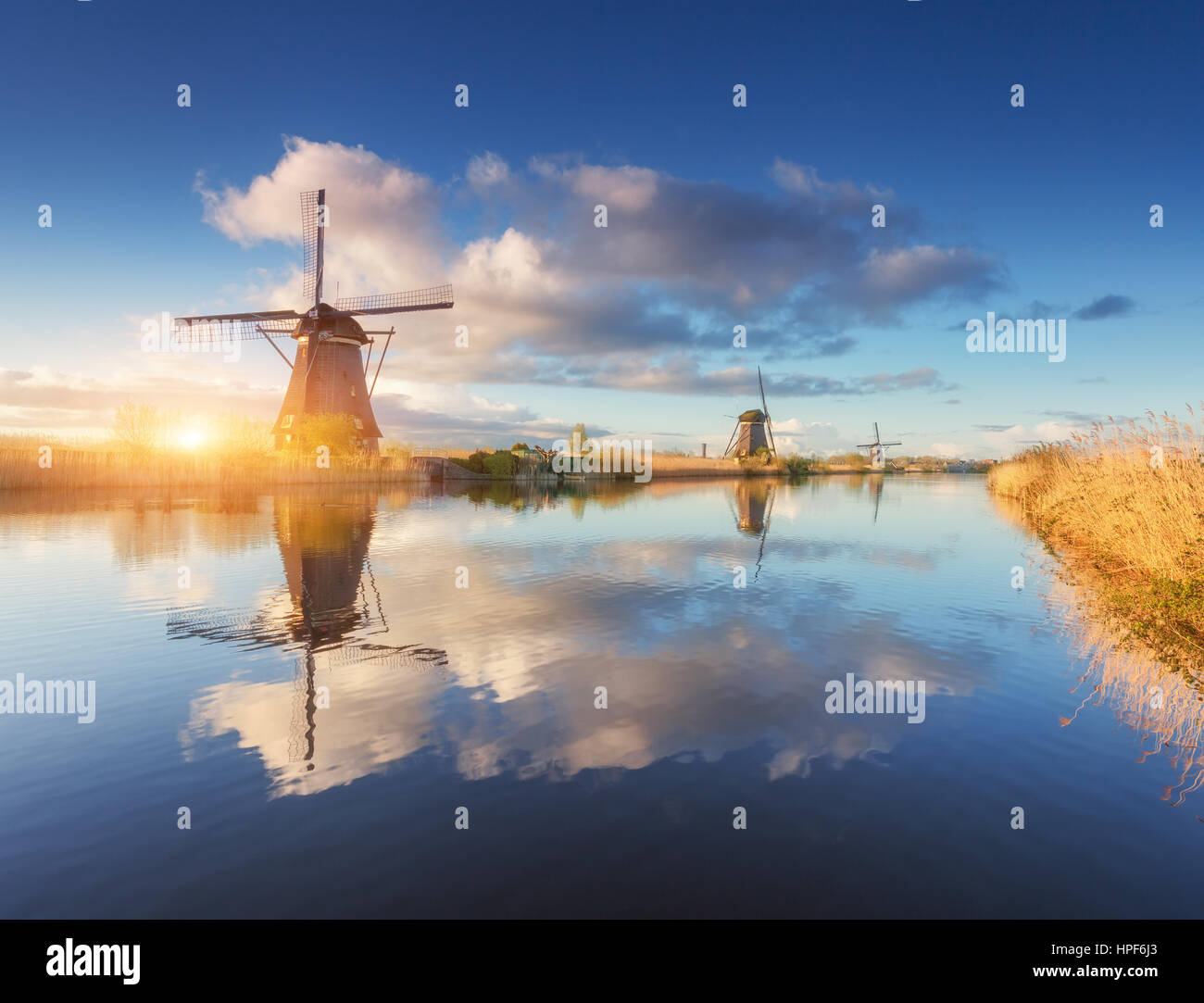 Windmills at sunrise. Rustic landscape with amazing dutch windmills near the water canals with blue sky and clouds - Stock Image