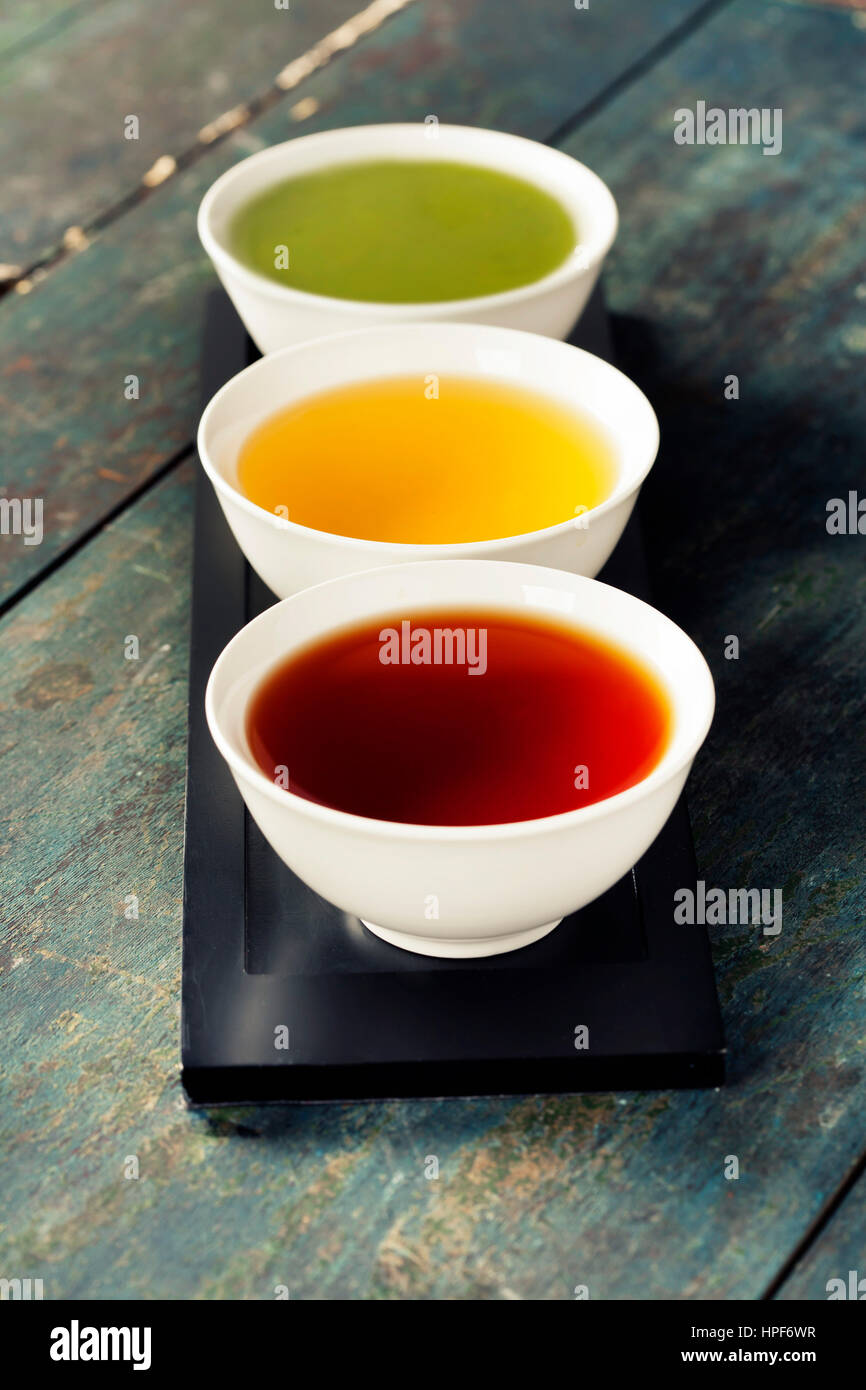 Tea concept. Different kinds of tea (black, green and matcha tea) in ceramic bowls on wooden background Stock Photo
