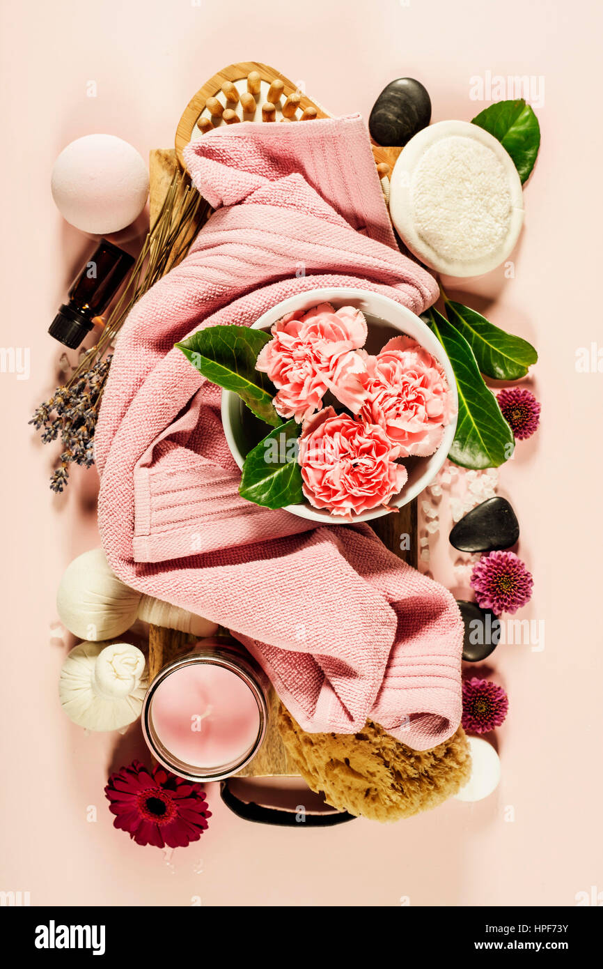 Spa background with sea salt, bowl ,flowers, water, soap bar, candles, essential oils, massage brush and flowers,top - Stock Image
