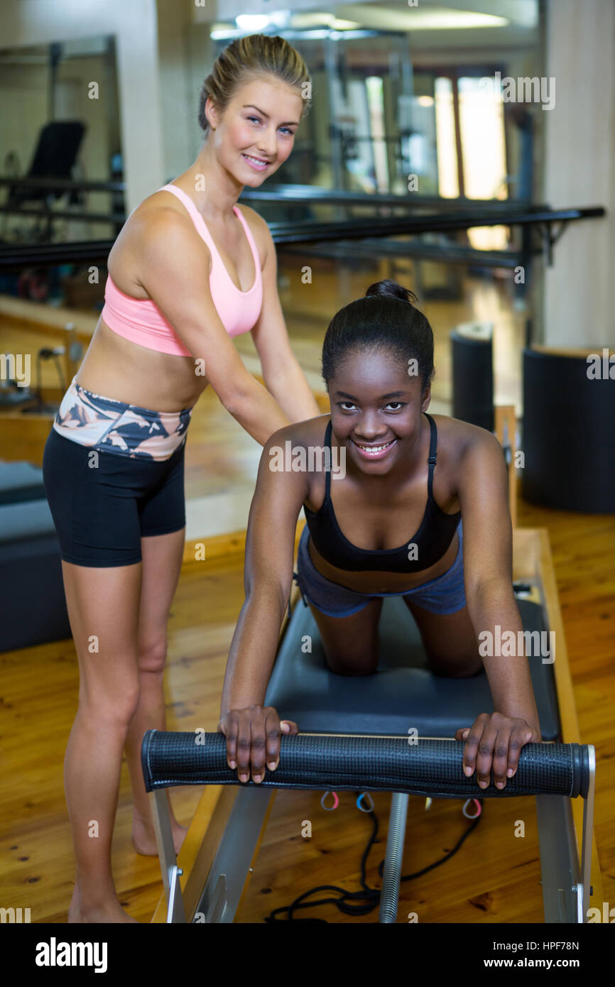 Smiling trainer assisting woman with pilates on reformer in fitness studio - Stock Image