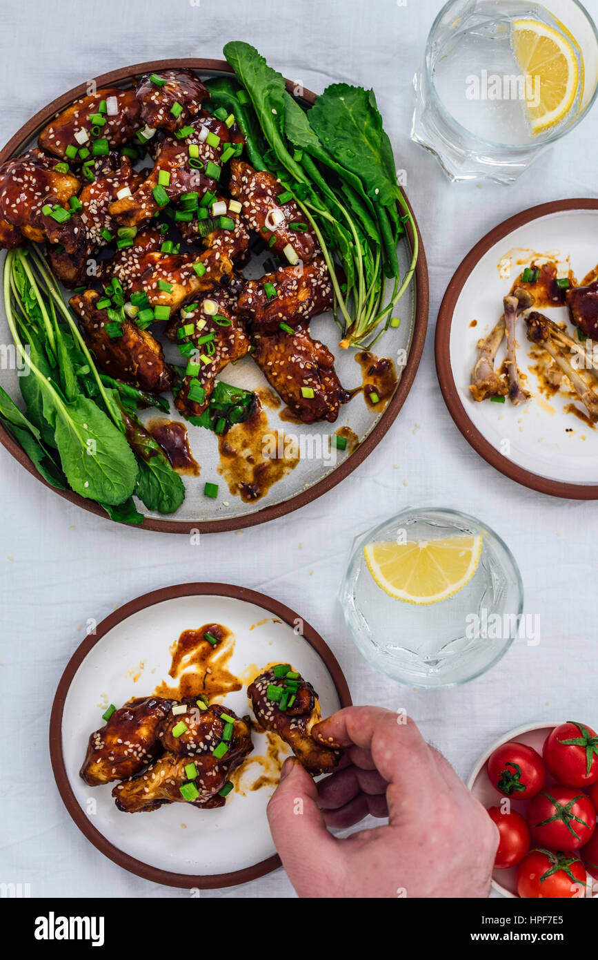 Oven-baked chicken wings with a sticky sauce and sesame seeds served with herbs on one large plate and two small - Stock Image