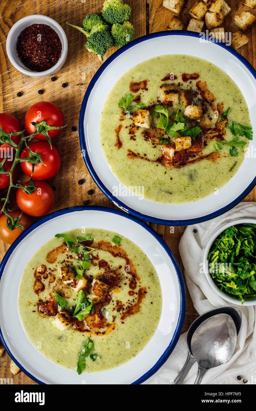 Cream of broccoli soup in two white bowls, garnished with a chili powder sauce, croutons and parsley. Accompanied - Stock Image
