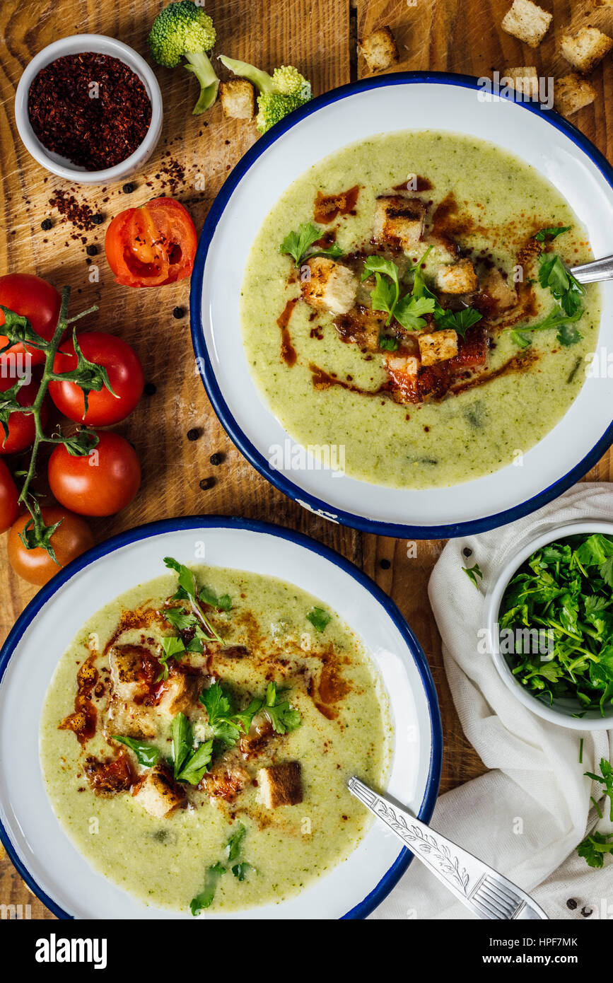 Cream of broccoli soup in two white bowls with spoons, garnished with a chili powder sauce, croutons and parsley. - Stock Image