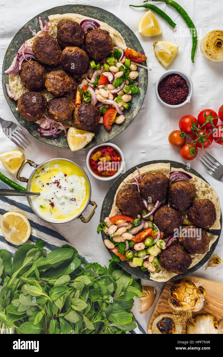 Turkish meatballs aka koftes served on pita bread on two copper plates with cold bean salad and red onions photographed Stock Photo