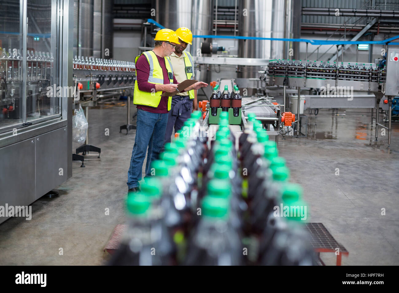 Two factory workers monitoring cold drink bottles on production line at drinks production plant Stock Photo