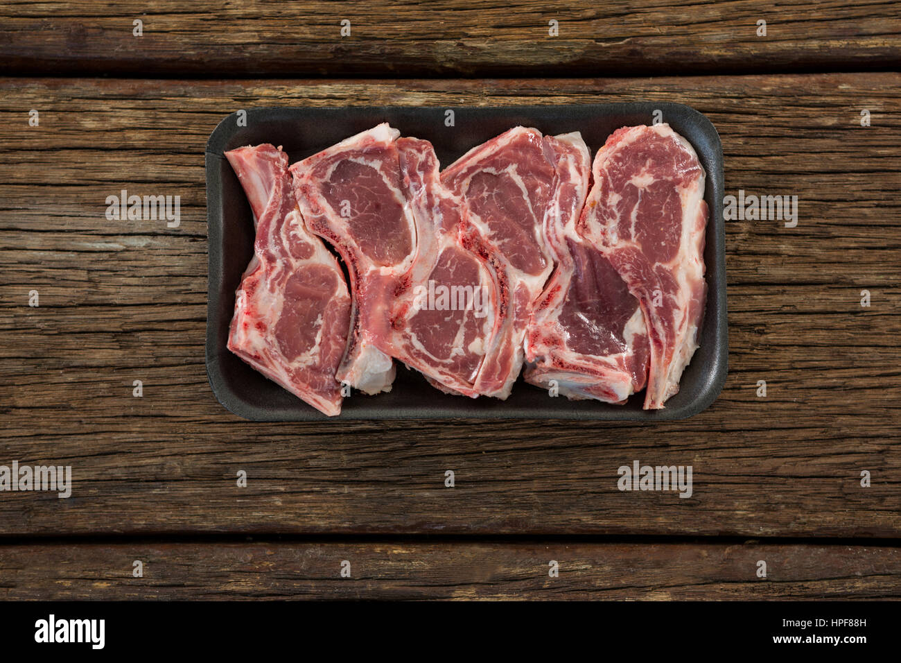Raw Sirloin chop in black box against wooden background - Stock Image