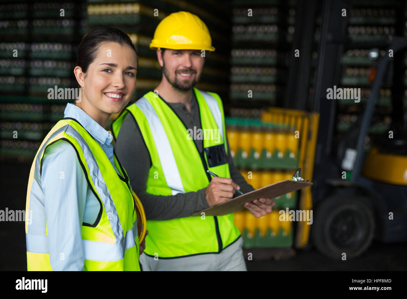 Portrait of factory workers discussing inventory over clipboard at drinks production factory - Stock Image