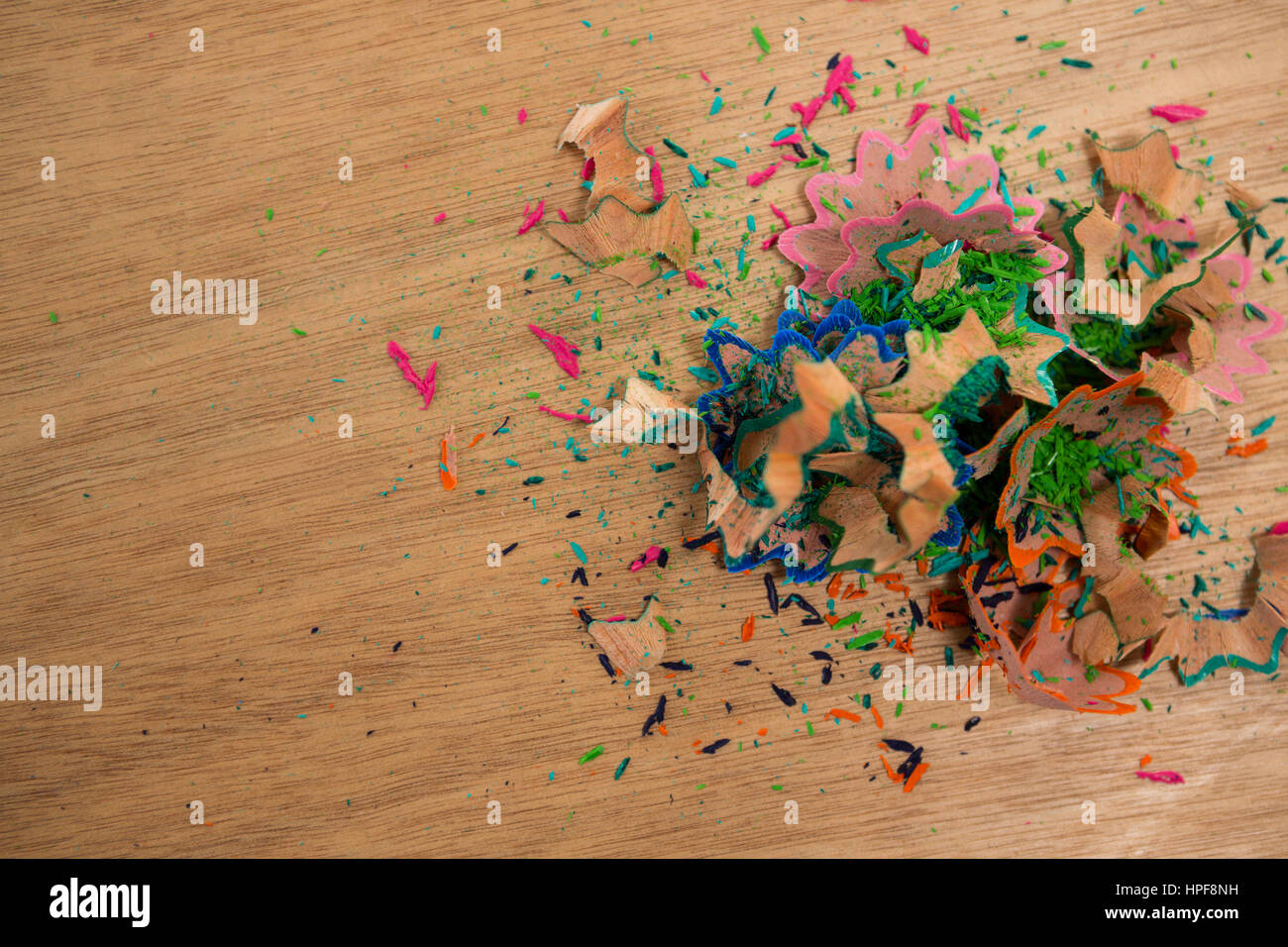 Close-up of colored pencil shavings on wooden background - Stock Image