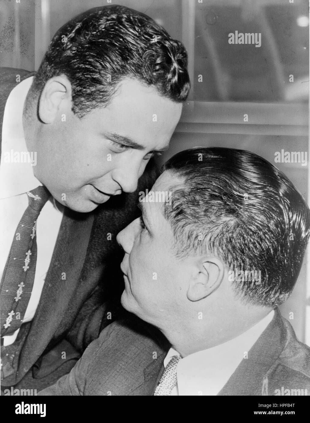 Wiretap expert Bernard Spindel whispers in ear of James R Hoffa after court session in which they pleaded innocent - Stock Image