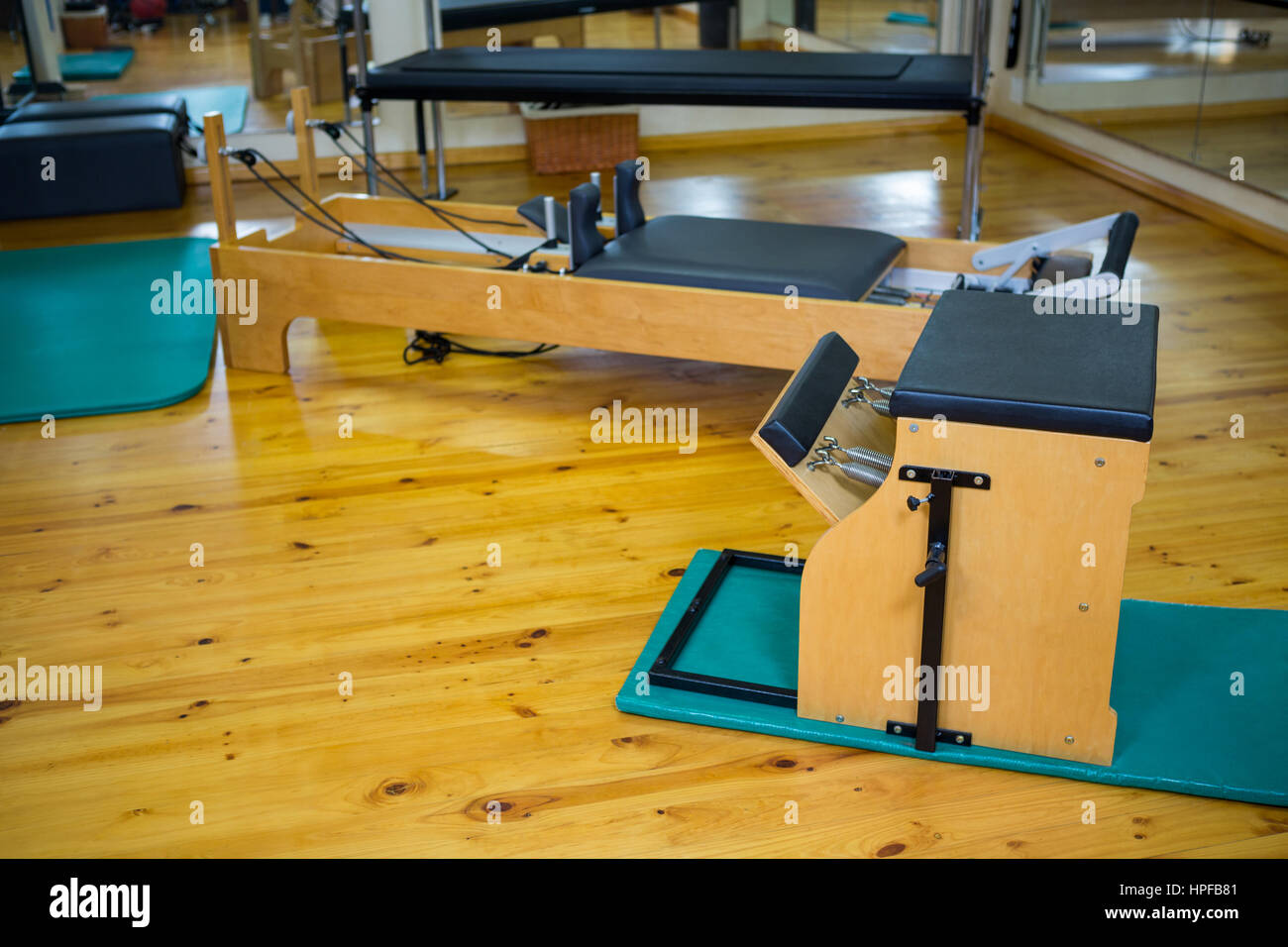 Reformer and wunda chair on wooden floor in gym - Stock Image