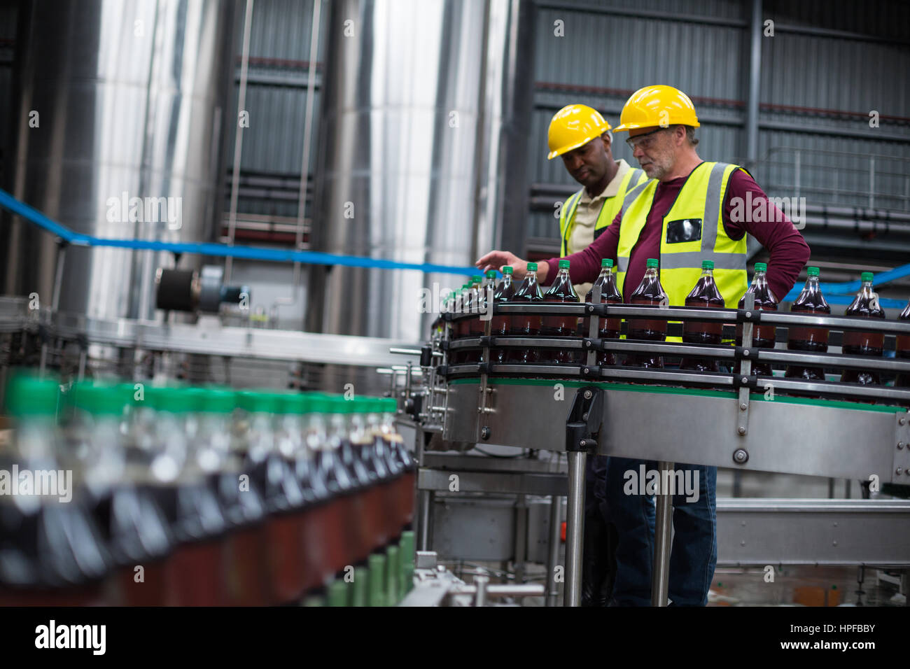 Two factory workers monitoring cold drink bottles at drinks production plant - Stock Image