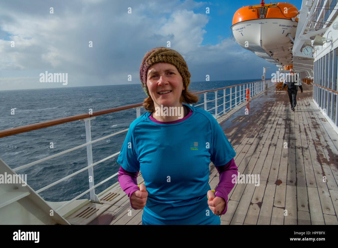 Woman jogging on the QM2's promenade deck. Crossing the slate grey North Atlantic ocean on the liner Queen Mary - Stock Image